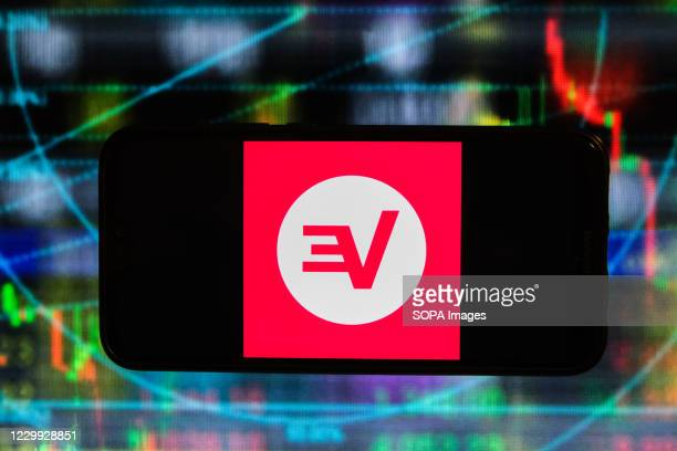In this photo illustration an Express VPN logo is displayed on a smartphone with stock market graphics on the background.