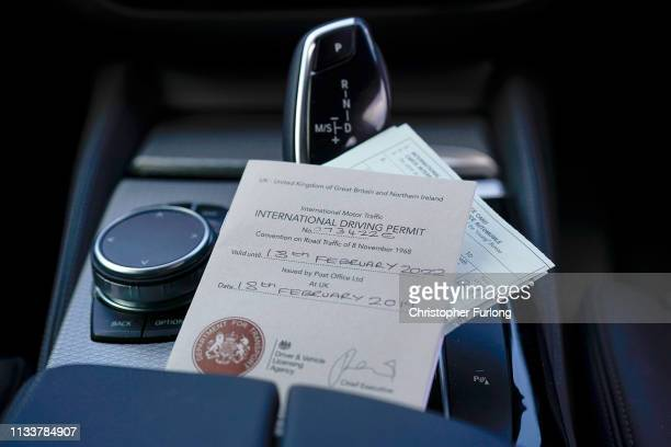 In this photo illustration an International Driving Permit and an International Motor Insurance Certifcate, known as a 'green card' sit inside a car...