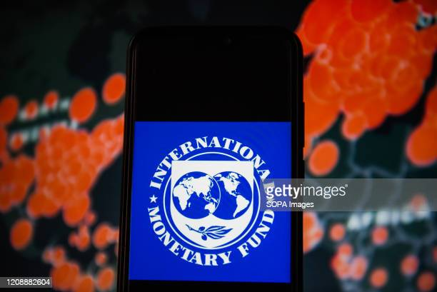 In this photo illustration an International Monetary Fund logo is seen displayed on a smartphone with a World map of COVID 19 epidemic on the...