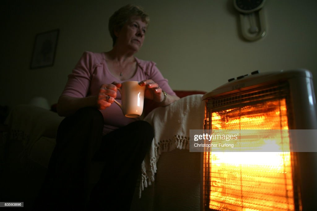 In this photo illustration an old age pensioner keeps warm with the aid of an electric heater on November 6, 2008, in Conwy, Wales. With the recent high rise in fuel and energy bills many senior citizens are facing a cold winter. The UK's National pensioner Convention has called for a higher basic state pension for the over 60's.