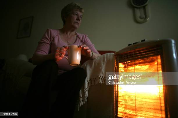 In this photo illustration an old age pensioner keeps warm with the aid of an electric heater on November 6 in Conwy Wales With the recent high rise...
