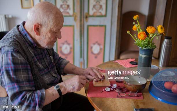 In this photo illustration an old man is cutting onions at his table in a living room on March 11, 2021 in Heidelberg, Germany.