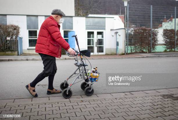 In this photo illustration an old man walking with a rolator, carrying his shopping home on January 23, 2021 in Heidelberg, Germany.