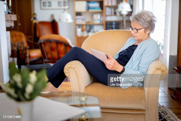 In this photo illustration an old woman sits comfortably in an armchair and looks into an ipad on May 12 2020 in Radevormwald Germany