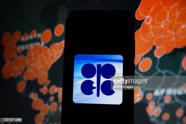 In this photo illustration an OPEC logo seen displayed on a smartphone with a World map of COVID 19 epidemic on the background