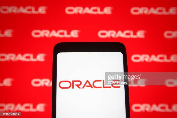 In this photo illustration an Oracle logo is seen on a smartphone and a pc screen.