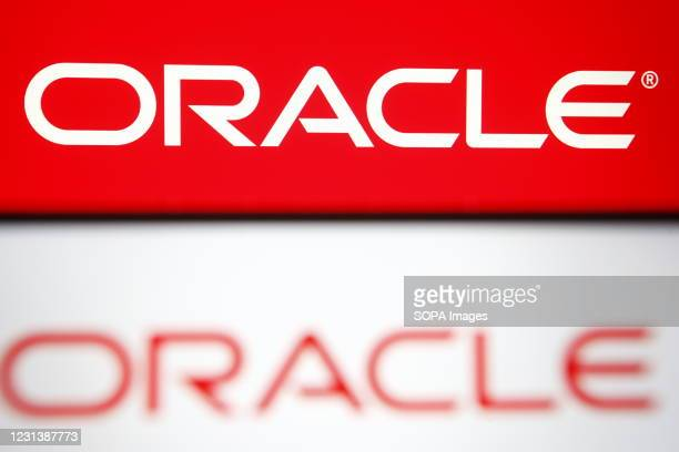 In this photo illustration an Oracle logo of a US multinational computer technology corporation is seen on a smartphone and a pc screen.