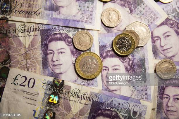 In this photo illustration banknotes of the pound sterling The Bank of England £20 notes with the image of Queen Elizabeth II and various coins of...