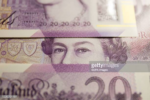 In this photo illustration banknotes of the pound sterling The Bank of England £20 notes with the image of Queen Elizabeth II are seen displayed
