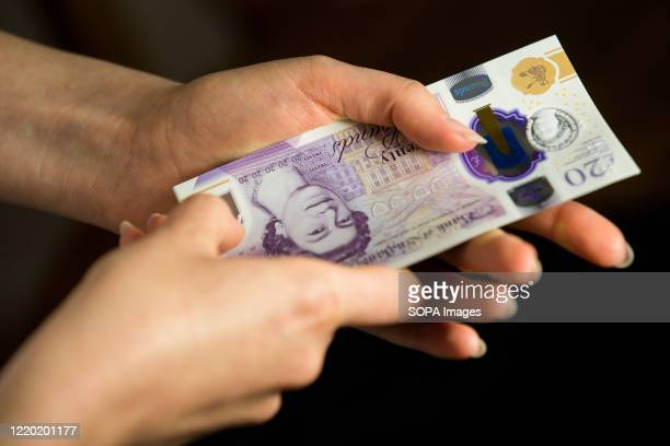 In this photo illustration banknotes of the pound sterling The Bank of England £20 notes with the image of Queen Elizabeth II are seen in a woman's...