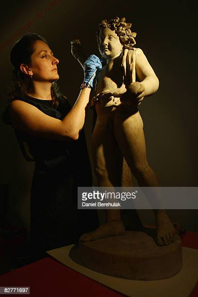 In this photo illustration British Museum Conservator Amy Drago works on a marble sculpture of a goatskin clad Bacchus in conservation room three of...