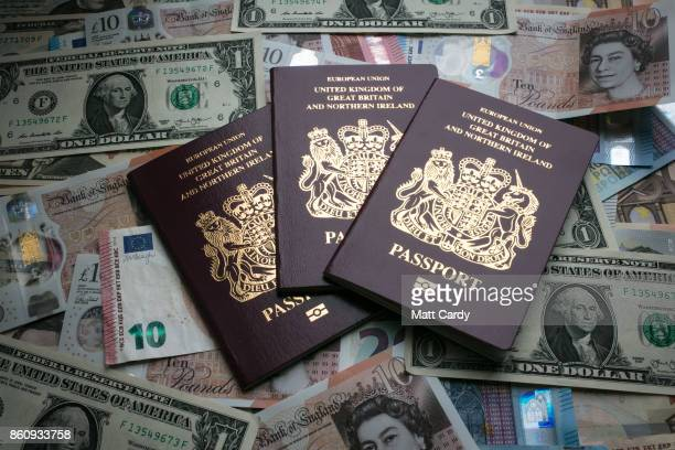 In this photo illustration British passports are placed on currency including the new £10 note US dollar bills and euro notes on October 13 2017 in...