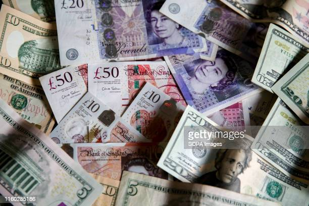 In this photo illustration British Pound sterling and US Dollar banknotes are seen as Pound to US Dollar exchange rates are now trading close to a 2...