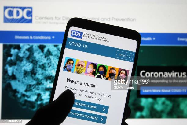 In this photo illustration Centers for Disease Control and Prevention website with people wearing facemasks is seen displayed on a smartphone with a...