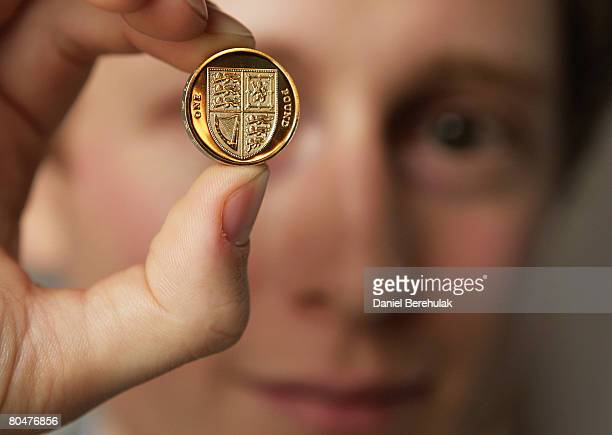 In this photo illustration competition winner Matthew Dent holds the new design one pound coin during a press launch on April 2 2008 in London...