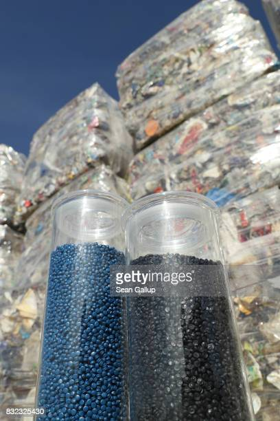 In this photo illustration containers of pellets derived from discarded plastics stand in front of bales of sorted trash at the ALBA sorting center...
