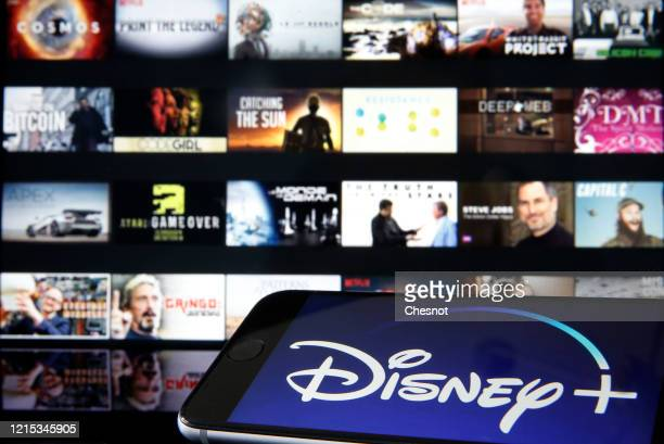 In this photo illustration, Disney + logo is diplayed on the screen of an iPhone in front of a television screen showing a Disney + logo on March 28,...