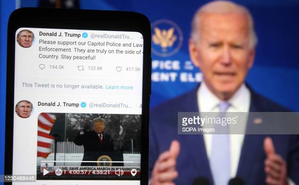 In this photo illustration, Donald Trump Twitter messages are seen displayed on a smartphone screen in front of a fragment of a video with U.S....