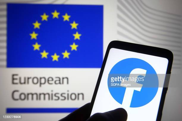 In this photo illustration, Facebook logo is seen on a smartphone screen in front of the European Commission logo in the background.