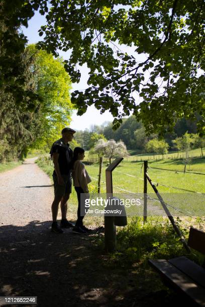 In this photo illustration father and daughter read an information board, which was placed at the edge of the forest on April 25, 2020 in...