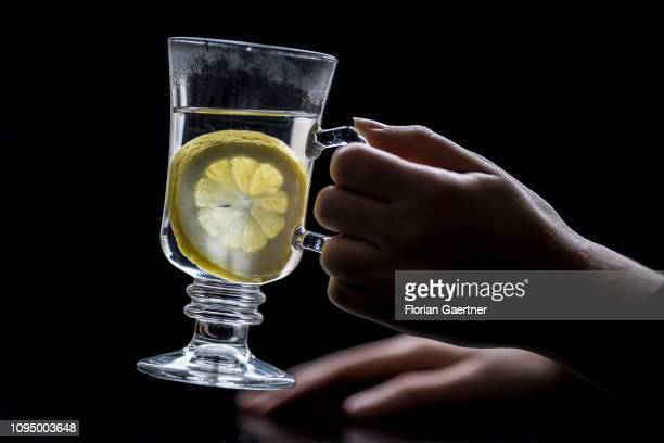 In this photo illustration female hands are pictured with a glas of hot lemon on February 05 2019 in Berlin Germany