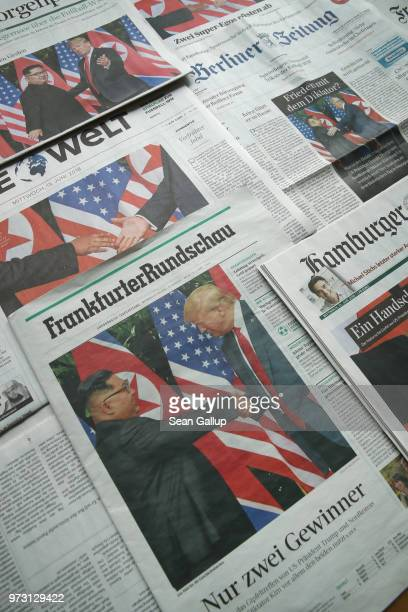 In this photo illustration German newspaper front pages from June 13 lie arranged and all show US President Donald Trump meeting North Korean leader...