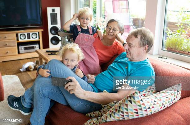 In this photo illustration Grandparents and grandchildren are looking at a smartphone on July 27, 2020 in Bonn, Germany.