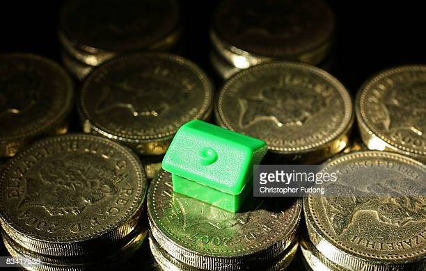 In this photo illustration, houses from a Monopoly board game sit on top of British currency coins on October 24, 2008 in Manchester, England. As...
