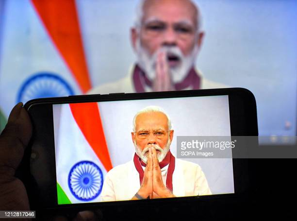 In this photo illustration Indian Prime Minister, Narendra Modi speaking to the Nation about Covid19 crisis on a smartphone. Prime Minister, Narendra...