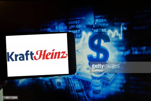In this photo illustration is seen the logo of Kraft Heinz is seen on a screen next to a colorful illustration of money and the stock market The...