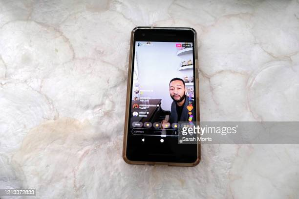 In this photo illustration John Legend is seen on a smart phone performing on Instagram Live during the coronavirus outbreak on March 16 2020 in Los...