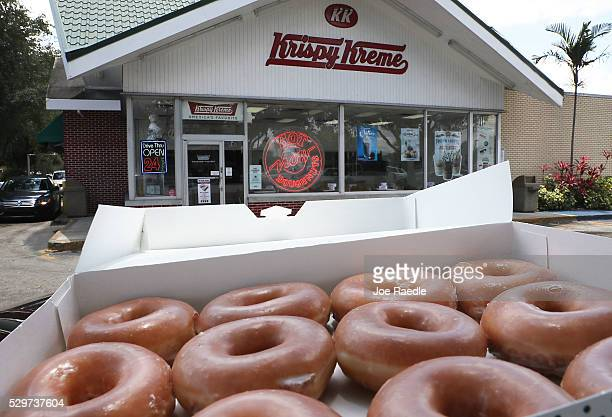 In this photo illustration Krispy Kreme Donuts are seen outside of a store on May 09 2016 in Miami Florida JAB Holdings Company announced it is...