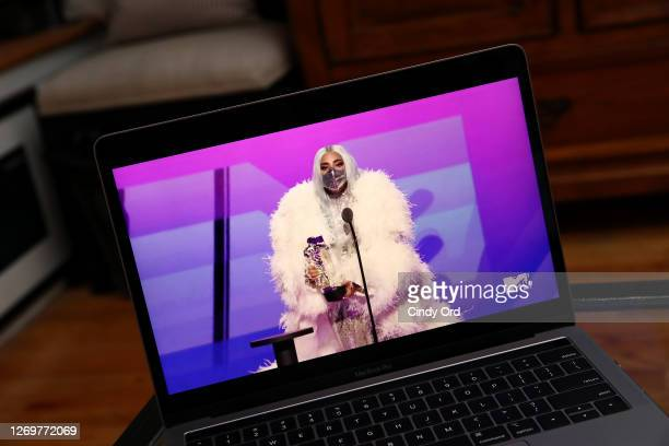 In this photo illustration Lady Gaga accepts the Artist of the Year award viewed on a laptop during the 2020 MTV Video Music Awards broadcast on...