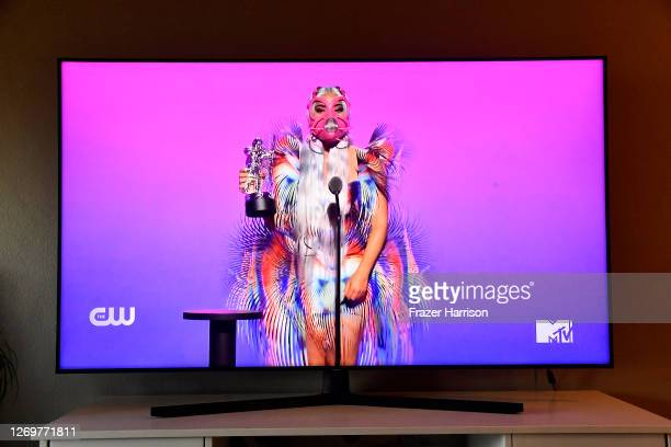 In this photo illustration Lady Gaga accepts the Best Collaboration award for Rain on Me with Ariana Grande viewed on a television screen during the...