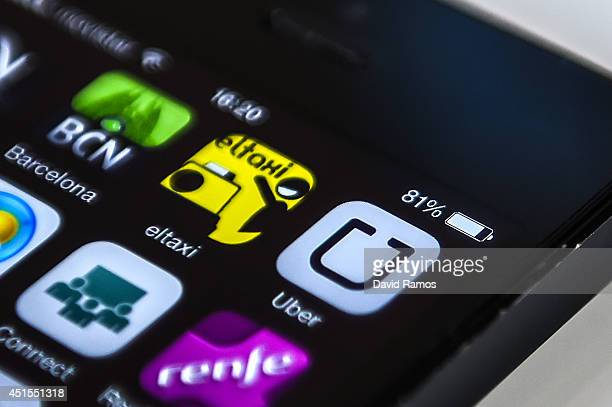 In this photo illustration logos of 'Uber' a Barcelona taxi and Barcelona City guide apps are seen in a smart phone on July 1 2014 in Barcelona Spain...