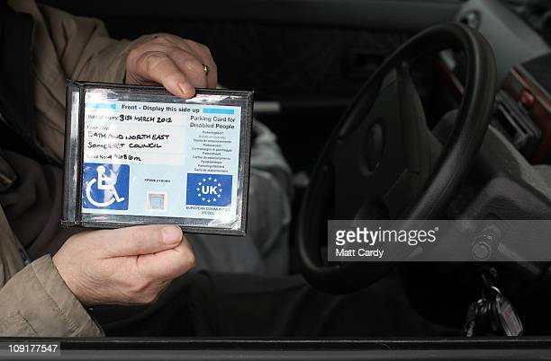 In this photo illustration Michael Bloom a disabled badge holder shows his parking badge as he waits in a disabled car parking bay in a supermarket...
