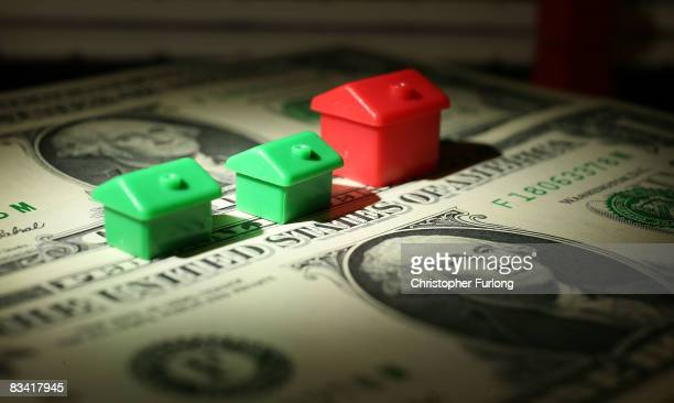 In this photo illustration miniature houses from a Monopoly board game can be seen next to American Dollar notes on October 23, 2008 in Manchester,...
