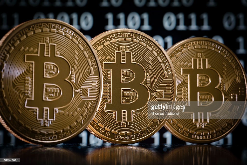 In this photo illustration model Bitcoins stands in front of a binary code on January 06, 2017 in Berlin, Germany.