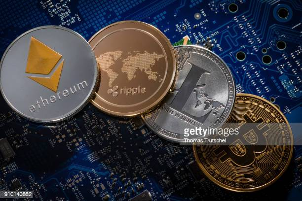 In this photo illustration model coins of the cryptocurrencies ethereum ripple litecoin and bitcoin lie on a circuit board of a computer on January...