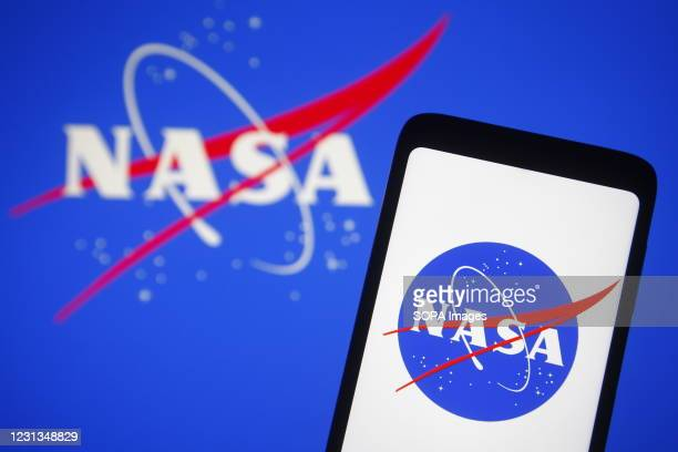 In this photo illustration, NASA logo is seen displayed on a smartphone and pc screen.