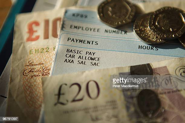 In this photo illustration notes and coins are displayed with a pay slip on February 17 2010 in London England As the UK gears up for one of the most...