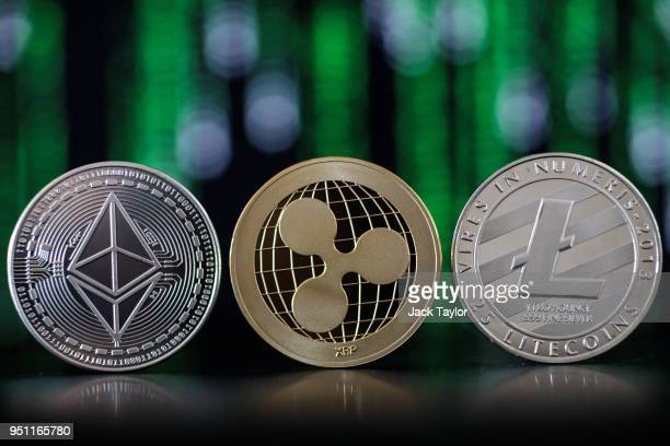 In this photo illustration of the ethereum, ripple and litecoin cryptocurrency 'altcoins' sit arranged for a photograph on April 25, 2018 in London,...
