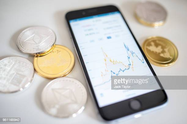 In this photo illustration of the litecoin ripple and ethereum cryptocurrency 'altcoins' sit arranged for a photograph beside a smartphone displaying...