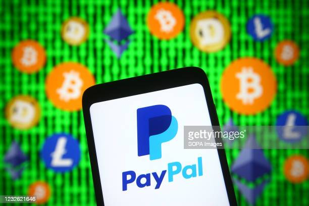 In this photo illustration, PayPal logo is seen displayed on a smartphone screen in front of cryptocurrency signs.