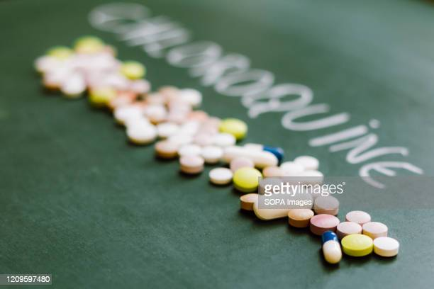 In this photo illustration pharmaceutical pills are seen displayed on a table with a Chloroquine inscription on the background