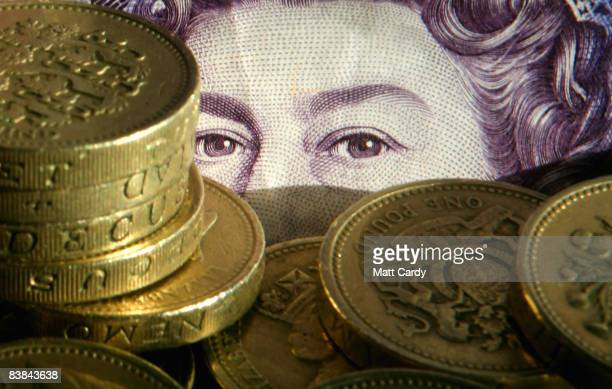 In this photo illustration pound coins are stacked in front of a twenty pound note on November 27 2008 in Bristol England Many UK consumers are...