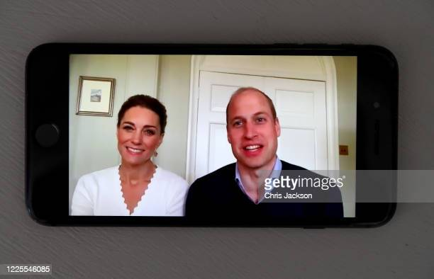 In this photo illustration Prince William Duke of Cambridge and Catherine Duchess of Cambridge speak to crisis volunteers on a videocall to mark the...