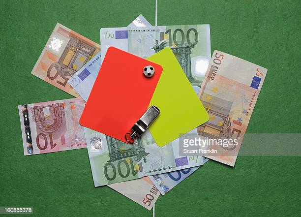 In this photo illustration, referee's red and yellow cards along with a whistle, Euro bank notes and a table soccer game are juxtaposed on February...