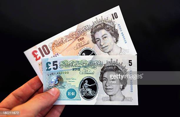 In this photo illustration sample Polymer five and ten pound British banknotes are held during a news conference at the Bank of England on September...