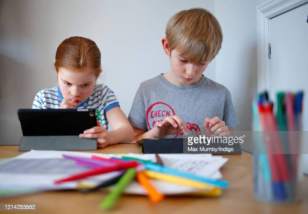 In this photo illustration, school- age children of the photographer use iPads to complete online schoolwork at home whilst schools are closed due to...